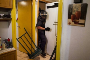Police remove the door and push refrigerator as they break into Maria Isabel Rodriguez Romero's apartment  to evict her and her family in Madrid, Spain, Wednesday, Sept. 25, 2013. Rodriguez Romero, 45 years old, has 6 family members, all unemployed including a 8 year-old daughter, and her mother with a bipolar syndrome. They live together in an apartment of the State City Hall Housing Company (EMVS) for 24 years and they have paid a debt of 1200 euros but EMVS informed them they have to move out. EMVS, a state company with an aim to give housing solutions for people in need, sold 1.860 state apartments to private investors in 2013. The eviction was executed despite of the resistance of dozens of Victims' Mortgage Platform (PAH) activists. (AP Photo/Andres Kudacki)